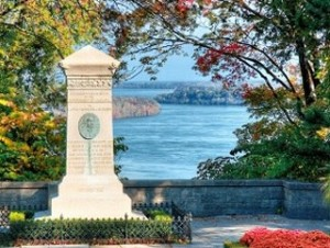 A view of the Lower Niagara River from Queenston Heights with a monument to War of 1812 herione in the foreground.