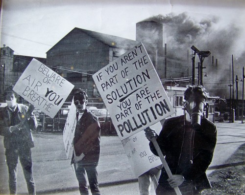 "Niagara At Large publisher and environment reporter Doug Draper with the gas mask and ""If you are not part of the solution"" sign, demonstrating in front of a then polluting Union Carbide plant in Welland, Ontario on the first Earth Day, April 22, 1970."