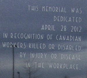 An inscription on a memorial in front of Niagara, Ontario's regional government headquarters. Flags in front of the building were lowered to half mast out of respects for workers who have been killed or injured on the job.