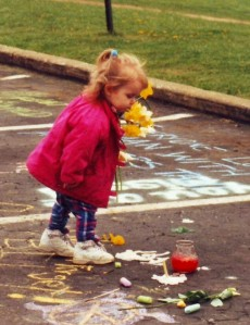 At the 25th commemoration ceremonies in 1995 for the 1970 Kent State shootings, a little girl places flowers on a spot where one of four students fell dead. Photo by Doug Draper