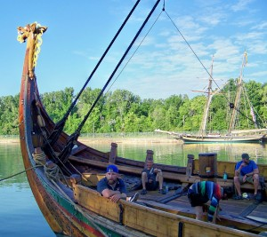Crew member Thomas Olsen (left) on board the Viking ship Draken Harald Harfagre in Niagara community of Port Weller at head of Welland Canada. A reproduction of the War of 1812 ship Pride of Baltimore is docked in the background. Photo by Doug Draper