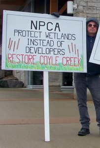 Niagara resident holds sign outside recent NPCA board meeting.